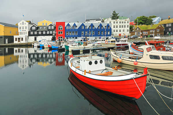 Colorful houses around a small fishing harbor with colorful boats Photograph by Rainer Grosskopf