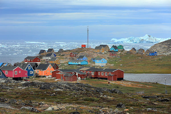 Colorful Wooden Houses Of A Tiny Little Town On A Cloudy Day With Icebergs Floating In The Sea In The Background Photograph by Rainer Grosskopf