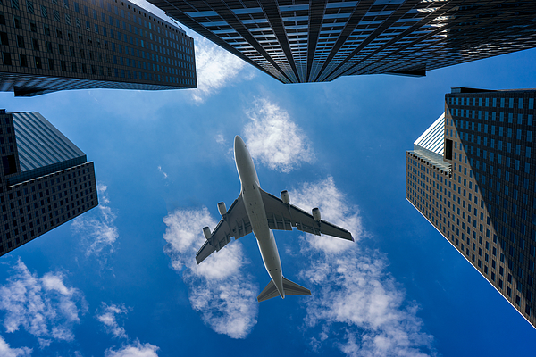 Commercial airplane flying over modern building Photograph by Mongkol Chuewong