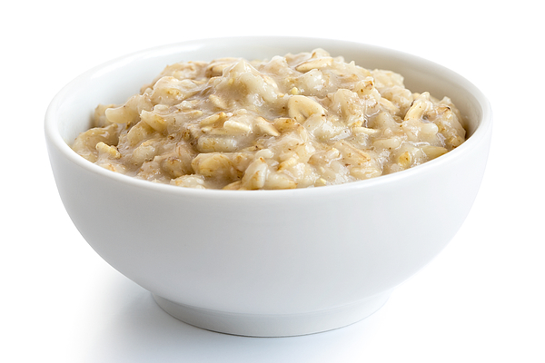 Cooked whole porridge oats in white ceramic bowl isolated on white. Photograph by Etienne Voss