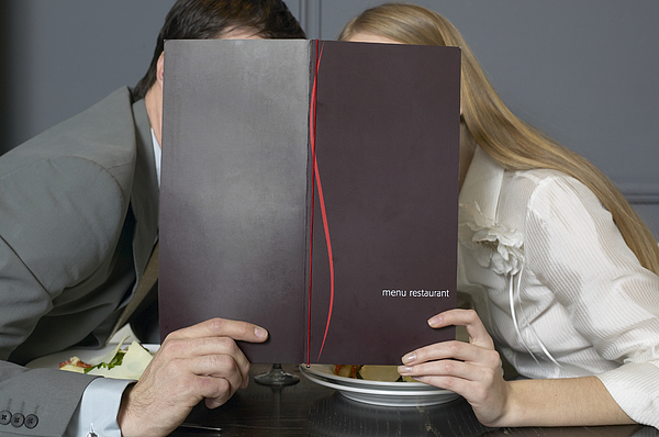 Couple at restaurant table leaning towards each other behind menu Photograph by Elke Hesser