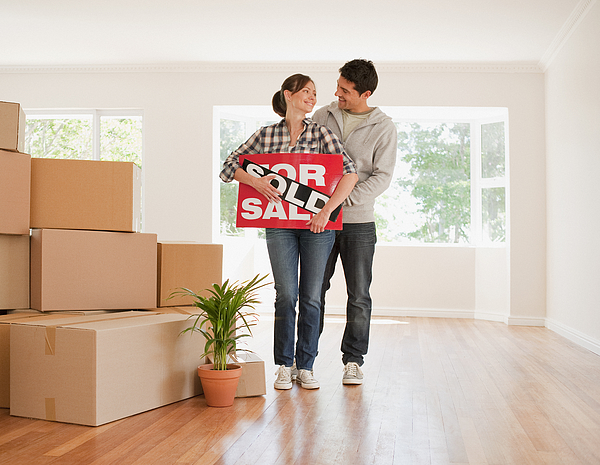 Couple holding sold sign for their new house Photograph by Martin Barraud