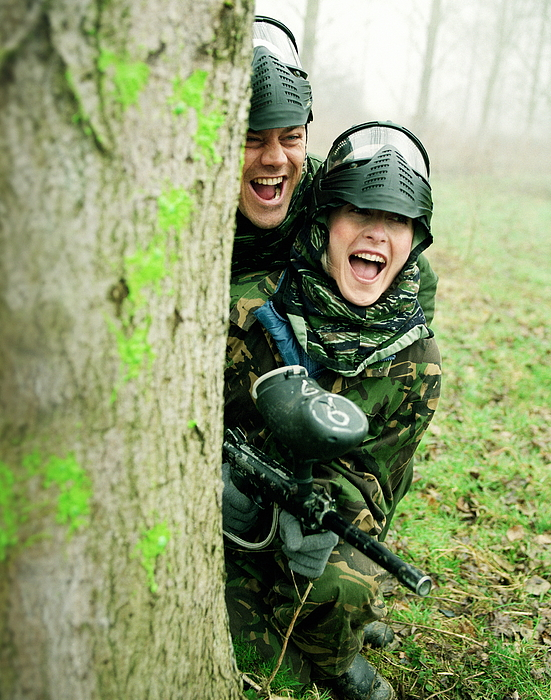 Couple paintballing, hiding behind tree Photograph by Alan Thornton