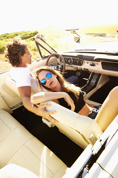 Couple relaxing in convertible outdoors Photograph by Colin Anderson Productions pty ltd