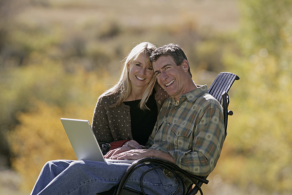 Couple Using Laptop Photograph by Comstock Images