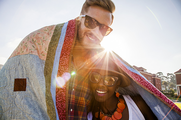 Couple wrapped in blanket smiling outdoors Photograph by Adam Hester