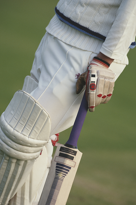 Cricketeer holding bat, low section, side view Photograph by Yellow Dog Productions
