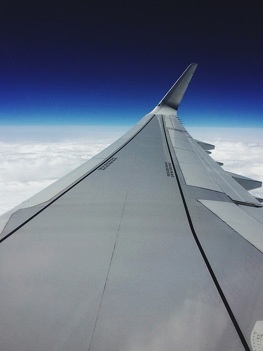 Cropped Image Of Airplane Flying Above Clouds In Sky Photograph by Tim Chong / EyeEm