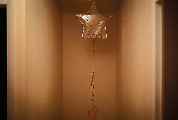 Cropped Image Of Woman Holding Star Shape Helium Balloon Photograph by Alessandro Miccoli / EyeEm