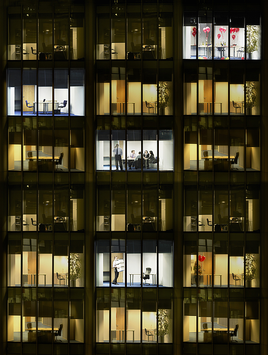 Cross section of office block with people working, view from building exterior (full frame) Photograph by Moodboard