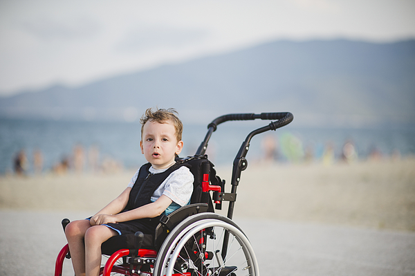 Cute young boy on the wheelchair by the sea Photograph by Dmphoto