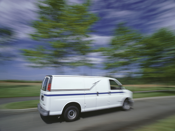 Delivery van travelling on country road Photograph by Ryan McVay