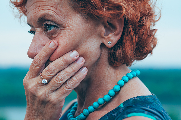 Depressed mature woman feeling alone outside Photograph by Marjan_Apostolovic