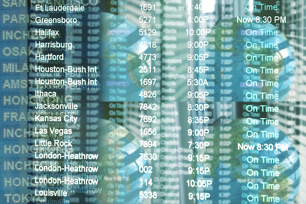 Destination board information at airport, overlaid onto four globes Photograph by RooMtheAgency