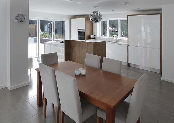 Dining table in open plan house Photograph by Image Source