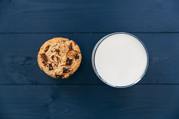 Directly Above Shot Of Cookie And Milk Glass On Table Photograph by Tom Eversley / EyeEm