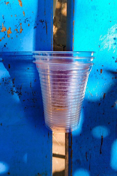 Disposable clear plastic cups left in a public bench. Photograph by CRMacedonio