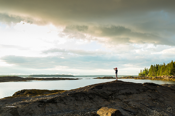 Distant view of senior man looking through binoculars at coast of Maine, USA Photograph by Heshphoto