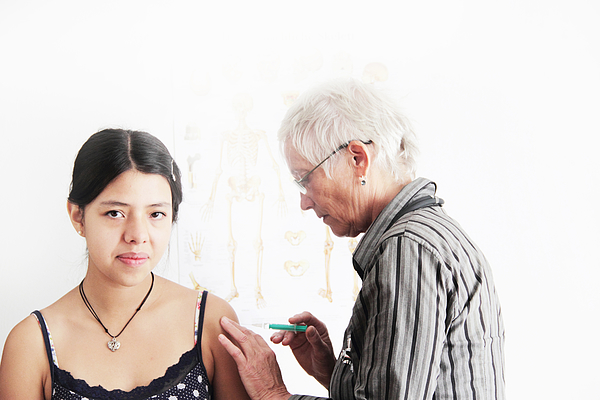 Doctor giving teenage girl shot Photograph by Sigrid Gombert