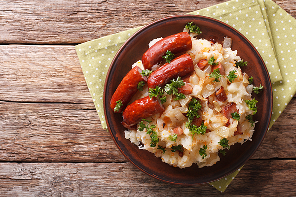 Dutch stamppot of potatoes, cabbage and carrots, with sausages closeup on a plate. horizontal top view Photograph by Alleko
