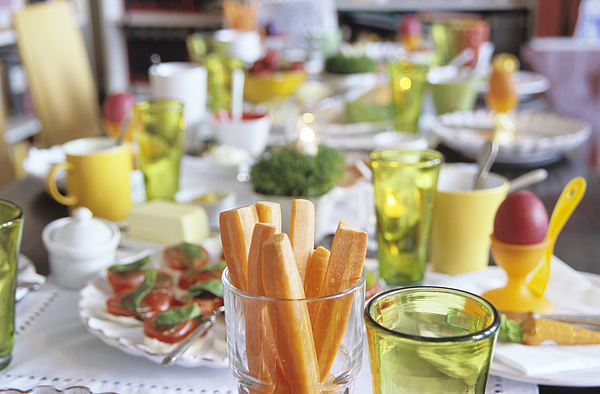 Easter table setting, focus on carrot slices in glass Photograph by Nico Hermann