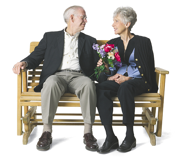 Elderly Couple Sit On A Bench And Gaze Lovingly Into Each Others Eyes. Photograph by Photodisc