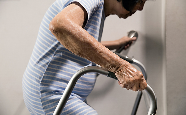 Elderly woman holding on handrail and walker for safety walk steps Photograph by Toa55