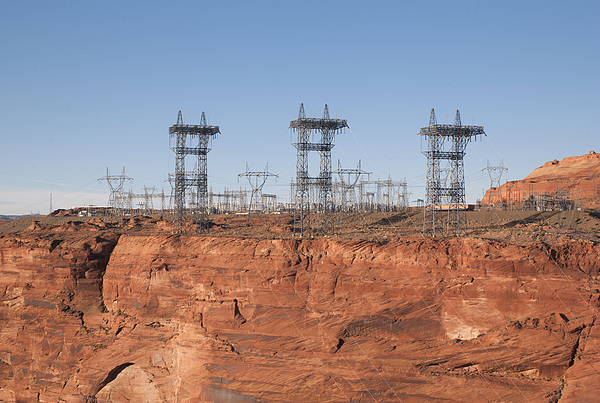 Electricity pylons over a dam Photograph by Fotosearch