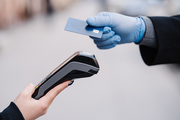 Faceless human in medical gloves during coronavirus epidemic, holds plastic card, tries to makes cashless payment for safety, uses modern technology. Pandemic, virus and prevention concept Photograph by Viorel Kurnosov