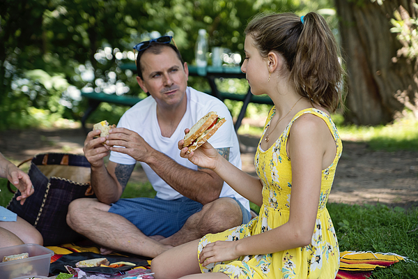 Family enjoying a picnic in public park in summer. Photograph by Martinedoucet
