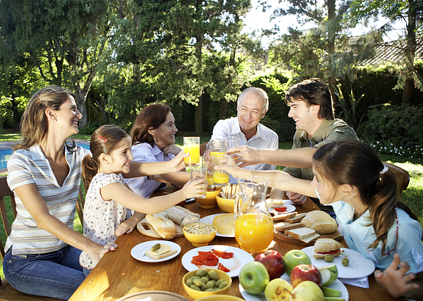 Family, Including Children (7-11) Sitting At Table In Garden, Toasting With Orange Juice And Smiling Photograph by Maria Teijeiro