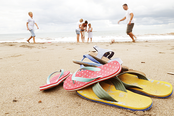 Family on beach, flip-flops in foreground Photograph by Peter Cade