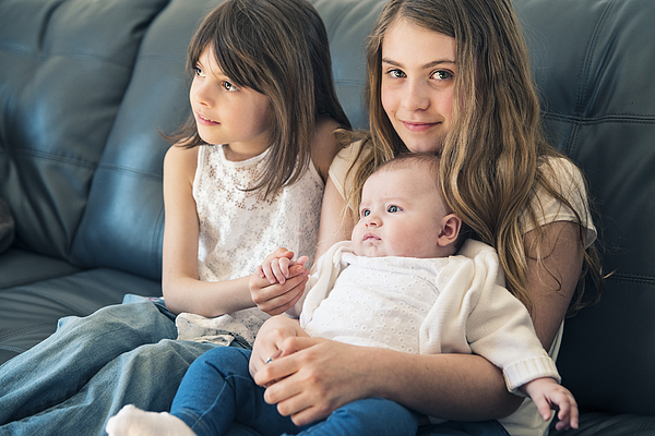 Family portrait of three sisters sitting on couch at home. Photograph by Martinedoucet