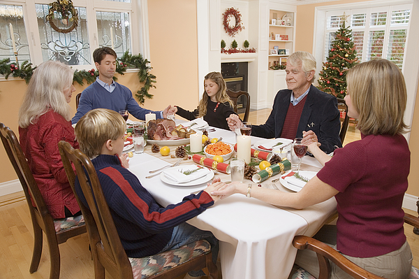 Family praying before Christmas dinner Photograph by Zoomphotographics