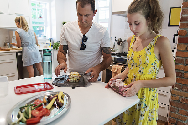 Family preparing lunch with eco-friendly food wrap. Photograph by Martinedoucet
