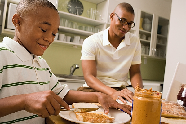 Father and son in eating in kitchen Photograph by Image Source
