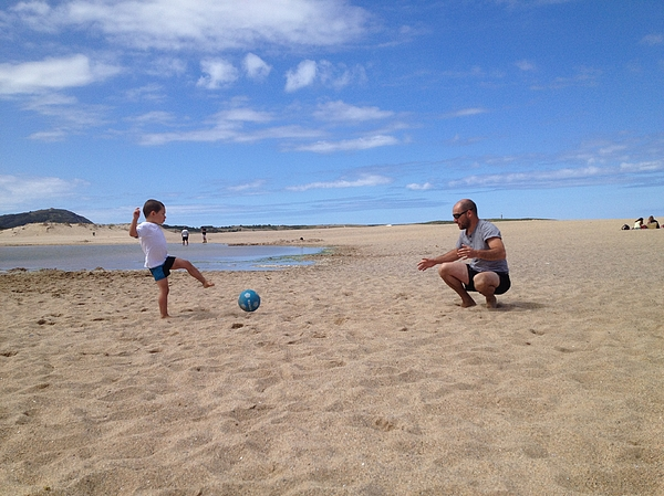 Father and son playing football on the beach Photograph by Amaia Arozena & Gotzon Iraola