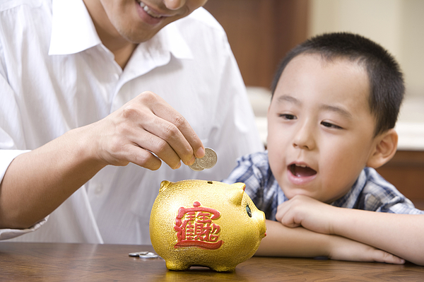 Father and son saving coins into a piggy bank Photograph by Lane Oatey