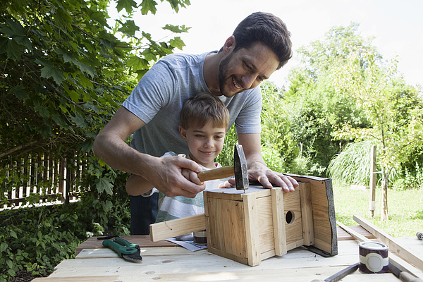 Father and son timbering a birdhouse Photograph by Westend61