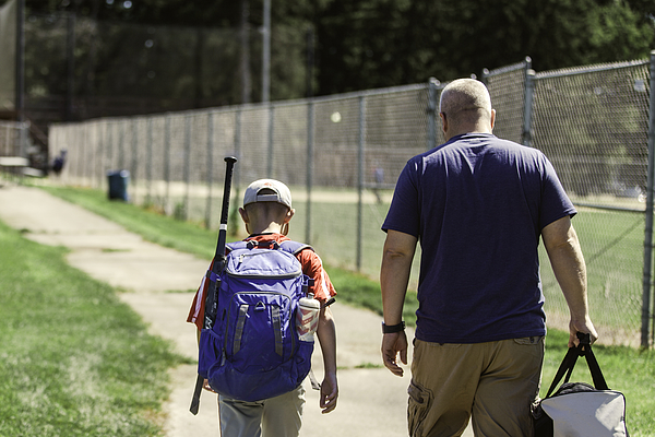 Father And Son Walking On Paved Path To Baseball Diamond Carrying Baseball Equipment Photograph by Rebecca Nelson