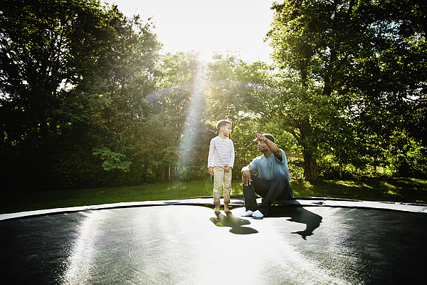 Father with young son on trampoline Photograph by Thomas Barwick