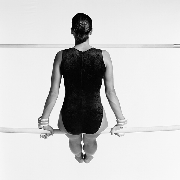 Female sitting on uneven bars, rear view, b&w. Photograph by Dominique Douieb