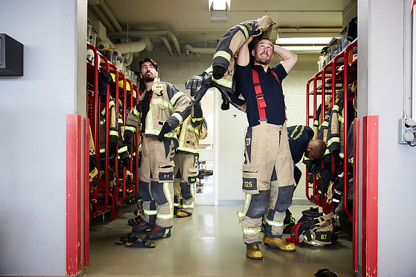 Firefighters wearing protective workwear in locker room while looking up at fire station Photograph by Maskot