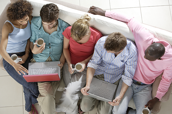 Five adults sat on sofa drinking tea with laptops Photograph by Peter Cade