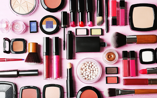 Flat lay of makeup cosmetics on pink background Photograph by Belchonock