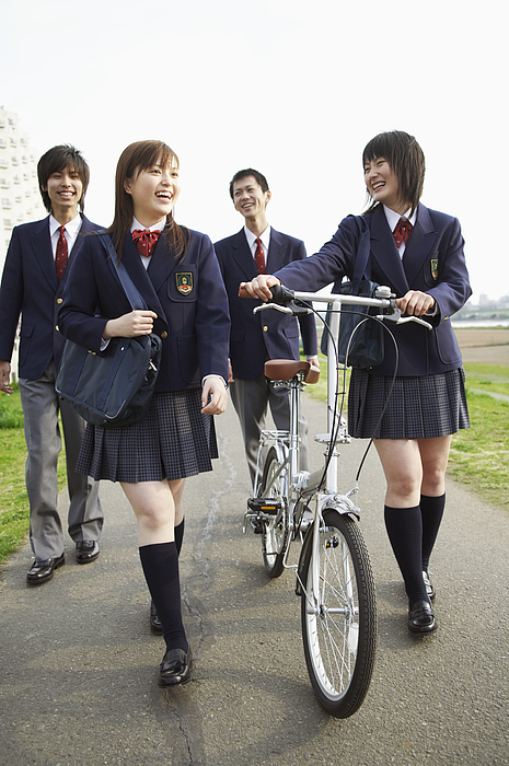 Four Students In Uniform Walking Outdoors, One Holding A Bicycle Photograph by Digital Vision.