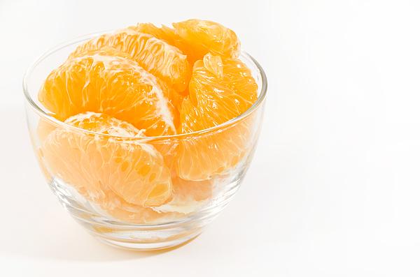 Fresh peeled Hassaku Orange in Transparent Glass bowl on white background Photograph by Karimitsu