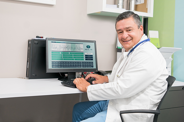 Friendly Male Doctor Completing A Medical History On Computer And Looking At Camera Very Happy Photograph by Andresr