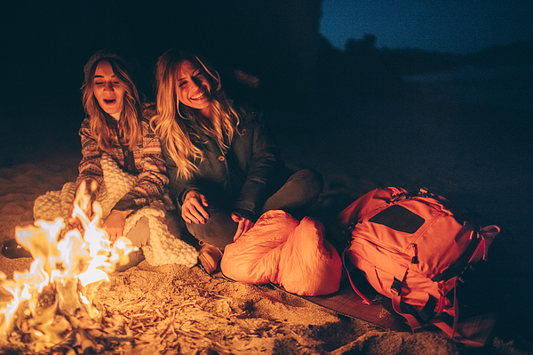 Friends enjoy evening on the beach by the log fire Photograph by AleksandarNakic