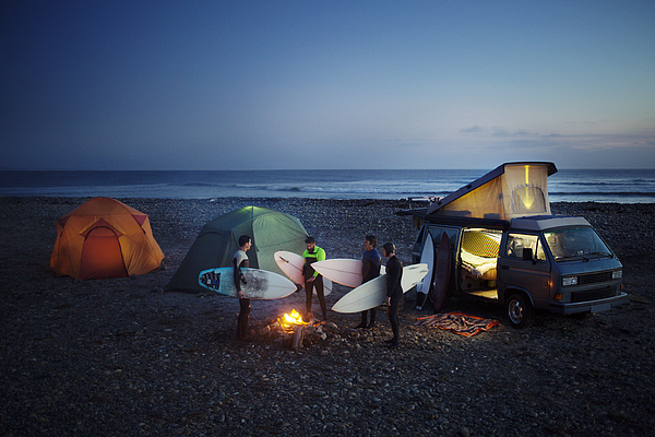 Friends with surfboard camping at beach against sky Photograph by Cavan Images